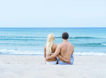 Loving couple sitting and embracing on summer beach Stock Image