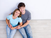 Loving couple sitting on the floor in embrace. Happy loving couple in embrace sitting on the floor in casuals- high angle Royalty Free Stock Images