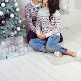 A loving couple is sitting on the floor near the New Year tree royalty free stock images