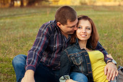 Loving couple sitting on the grass. Stock Photos