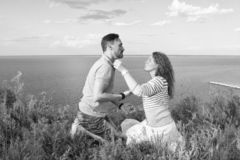 Loving couple sitting on grass face to face on knees. Young couple enjoying outdoors rest stock image
