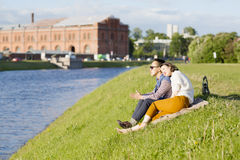 The loving couple is sitting on the grass. Royalty Free Stock Images