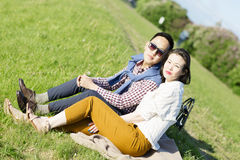 The loving couple is sitting on the grass. Stock Images