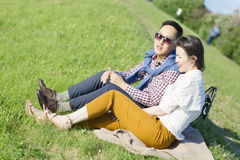 The loving couple is sitting on the grass. Royalty Free Stock Photos