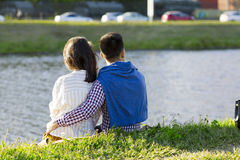 The loving couple is sitting on the grass. Royalty Free Stock Photography