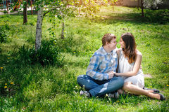 Loving couple sitting on grass in the spring sunny day Stock Image