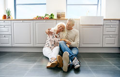Loving couple sitting on kitchen floor. Happy beautiful woman being held by her loving husband while sitting on kitchen floor Stock Image
