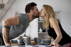 Loving couple sitting at a kitchen table, having a breakfast together Stock Images