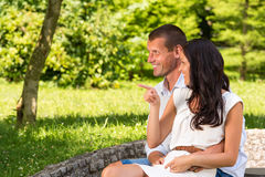 Loving couple sitting and laughing in park Royalty Free Stock Photography