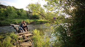 Loving couple sitting on a makeshift wooden bridge. Lovers man and woman on a romantic date in the countryside sitting on a wooden bridge stock footage
