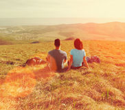 Loving couple sitting on meadow at sunny day Royalty Free Stock Image