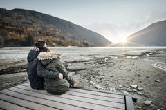 Loving couple sitting on a pier stock images