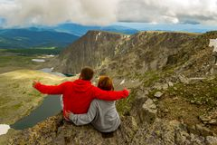 Loving couple sitting on a rock and embracing,the man is pointing at the colorful view of the mountains,the valleys of turquoise royalty free stock image