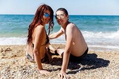Loving couple sitting at seashore Royalty Free Stock Photography