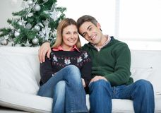 Loving Couple Sitting On Sofa During Christmas Stock Images