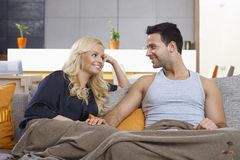 Loving couple sitting on sofa at home smiling. Young loving couple sitting on sofa at home, covered by blanket, smiling at each other with love stock photography