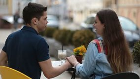 Loving couple sitting at street open-air cafe stock footage