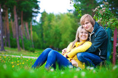 Loving couple are sitting in the sunny park Royalty Free Stock Images