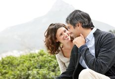 Loving couple sitting together in a park Stock Images