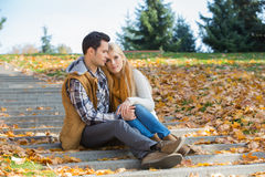 Loving couple sitting together on steps in park during autumn Royalty Free Stock Photo