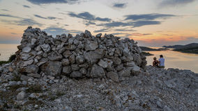 Loving couple sitting on top of a mountain, watching a beautiful sunset over the sea and islands. Kornati National Park. Royalty Free Stock Photo