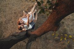 A loving couple is sitting under a tree royalty free stock photos