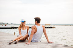 Loving couple sitting at the wooden pier Royalty Free Stock Photo