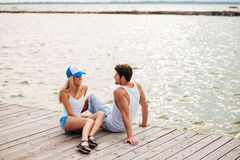 Loving couple sitting at the wooden pier Royalty Free Stock Photos