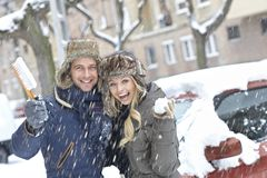 Loving couple smiling happy in snowfall Royalty Free Stock Images