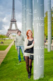 Loving couple smiling near the Eiffel Tower in Paris. Lovers smiling in Paris with the Eiffel Tower in the Background Royalty Free Stock Image