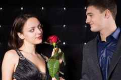 Loving couple smiling over a red rose Royalty Free Stock Image