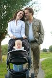 Loving couple smiling together and walking with baby outdoors Royalty Free Stock Photography