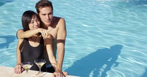 Loving couple smooching at swimming pool. While keeping martini glasses with olives on the side stock video footage