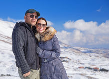Loving couple in snowy mountains Stock Images