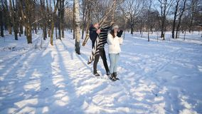 Loving couple in a snowy Park, caring young man covered his girlfriend with a blanket.  stock footage