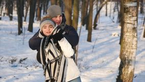 Loving couple in a snowy Park, caring young man covered his girlfriend with a blanket.  stock video