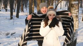 Loving couple in a snowy Park, caring young man covered his girlfriend with a blanket.  stock video footage