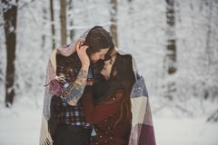 Loving couple in snowy winter forest Stock Photos