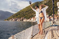 Couple spending happy time on a yacht at sea. Luxury vacation on a seaboat royalty free stock photography
