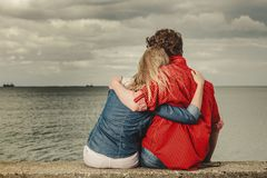 Couple sitting hugged on sea shore. Loving couple spending leisure time together at beach sitting on sea shore hugging rear view Stock Images