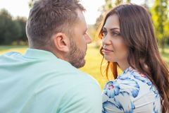 Loving couple is spending time with enjoyment. Forever together. Young attractive men and beautiful women are looking at each other with love. They are sitting Stock Photography