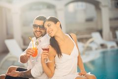 Loving couple spending vacation on tropical resort swimming pool.Newlyweds honeymoon on seaside. Couplr in true love.Flirting and showing emotions.Affection royalty free stock image