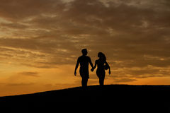 Loving couple of sportsmen walk on the evening hills. Silhouette of loving couple. Evening walk of husband and wife. Family walk Royalty Free Stock Image