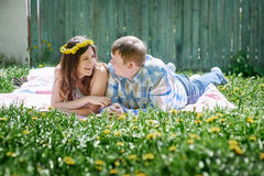 Loving couple in the spring garden on a picnic blanket to lie Royalty Free Stock Photo