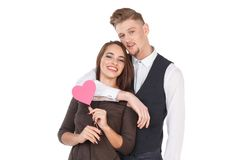 Loving couple stand and hug, the girl is holding a pink heart on a stick. Isolated on white. stock photography