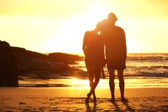 Loving couple standing by the beach looking at sunset. Full length portrait of a loving couple standing by the beach looking at sunset Stock Photo