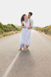 Loving couple standing on countryside road Royalty Free Stock Image