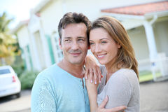 Loving couple standing in front of their house Royalty Free Stock Image