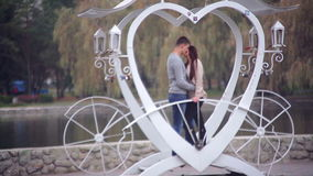 Loving couple standing in the gazebo in the form of heart. In the park. Valentine's Day stock footage