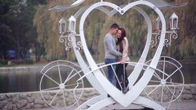 Loving couple standing in the gazebo in the form of heart. In the park. Valentine's Day stock video footage